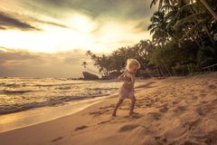 Cute child toddler girl walking on sunset beach during summer vacation concept happy childhood travel lifestyle stock images