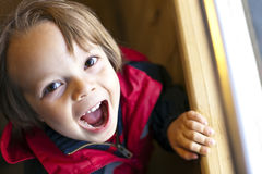 Cute Child with toothy smile. Selective focus and high contrast with available light Royalty Free Stock Photos