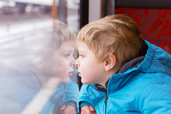 Cute child traveling and looking out train window outside. Cute child looking out train window outside, while it moving. Going on vacations and traveling by Royalty Free Stock Images