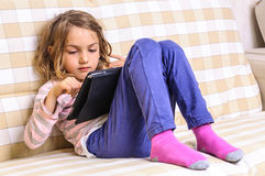 Cute child using tablet device Royalty Free Stock Image