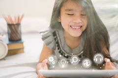 Cute child using a tablet and smiling while sitting on sofa at home stock images