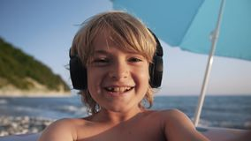 Cute child video chats on smart phone on beach