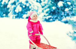Cute child walking with sled on snow in winter Stock Photo