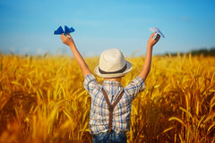 Cute child walking in the wheat golden field on a sunny summer d Stock Photography