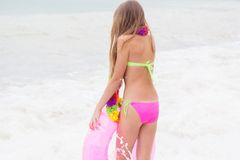 Cute child is wearing swimsuit walking at beach in Stock Photos
