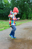 Cute child in wellingtons walking after rain Stock Image