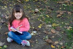 Cute child writing in notebook using pen and smiling. Four years old kid sitting on grass royalty free stock image