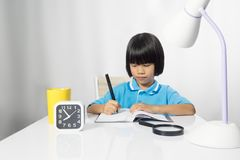 Cute child writing and working on work desk. stock image