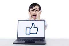 Cute child yelling with laptop on desk Stock Images