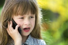 Cute child young girl talking on cellphone outdoors. Children and modern technology, communication concept.  stock photo