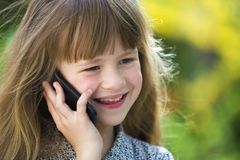 Cute child young girl talking on cellphone outdoors. Children and modern technology, communication concept.  royalty free stock photos