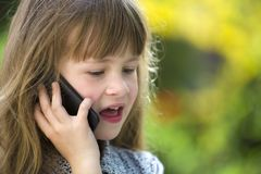 Cute child young girl talking on cellphone outdoors. Children and modern technology, communication concept.  stock images