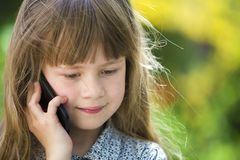 Cute child young girl talking on cellphone outdoors. Children and modern technology, communication concept royalty free stock photography