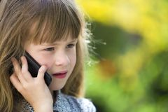 Cute child young girl talking on cellphone outdoors. Children and modern technology, communication concept stock images