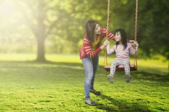 Cute child and young mother playing swing. Portrait of cute child and young mother playing swing in the park while laughing together royalty free stock image