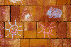 Cute childish drawing by chalk on red brick wall. Sun and clouds. Stock Photo
