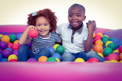 Cute children in ball pool holding balls Stock Photos