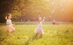 Cute children blowing a soap bubbles Royalty Free Stock Photos