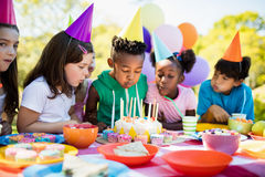 Cute children blowing together on the candle during a birthday party Stock Photos