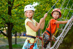 Cute children. Boy and girl climbing in a rope Royalty Free Stock Photos