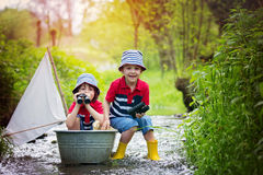 Cute children, boys, playing with boat and ducks on a little riv Royalty Free Stock Images