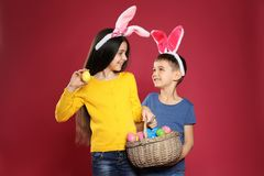 Cute children in bunny ears headbands holding basket with Easter eggs on color royalty free stock images