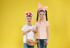 Cute children in bunny ears headbands holding basket with Easter eggs on color royalty free stock photography