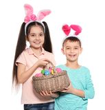Cute children in bunny ears headbands holding basket with Easter eggs on white stock images