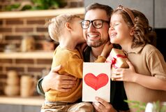 Cute children congratulating happy daddy with Fathers day and giving him handmade greeting postcard