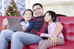Cute children and dad with laptop on sofa Royalty Free Stock Images