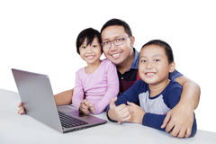 Cute children and dad with laptop on table Royalty Free Stock Photography