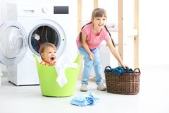 Cute children doing laundry. Indoors stock photo