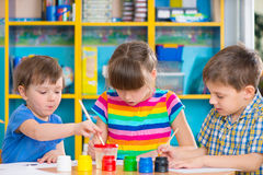 Cute children drawing with colorful paints at kindergarten Royalty Free Stock Image