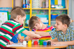 Cute children drawing with colorful paints at kindergarten royalty free stock photography