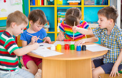 Cute children drawing with colorful paints at kindergarten Stock Images