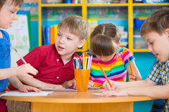 Cute children drawing with colorful paints at kindergarten royalty free stock photos