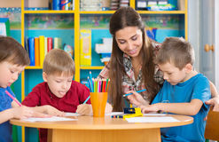 Cute children drawing with teacher at preschool class stock photos