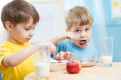 Cute children eat healthy food enjoying breakfast. At home royalty free stock photo