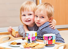 Cute children are eating dessert. Boy and girl are eating dessert Royalty Free Stock Images