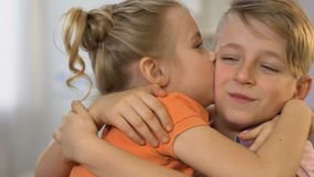 Cute children embracing, girl kissing boy on cheek, first love, happy together stock video
