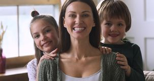Cute children embracing mom from behind, family portrait