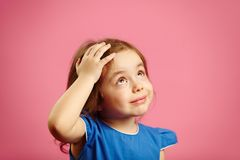 Cute children girl put her hand to head and looks up stock photography