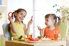 Cute children girls eating healthy food. Kids lunch at home or kindergarten. Cute children girls eating healthy food. Kids lunch at home, daycare center or royalty free stock image