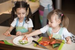 Cute children helping mother at kitchen. Adorable sisters making funny face with vegetables on plate. stock photo