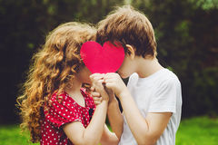 Cute children holding red heart shape in summer park. Valentines. Day background royalty free stock images