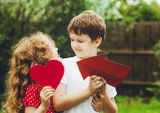Cute children holding red heart shape in summer park. Valentines Stock Image