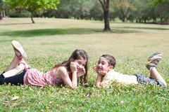Cute children lie down on green grass Royalty Free Stock Images