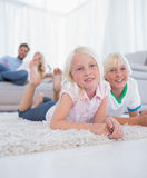 Cute children lying on the carpet smiling at camera Royalty Free Stock Images