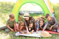Cute children with map near tent outdoors. Summer camp. Little children with map near tent outdoors. Summer camp royalty free stock image