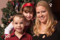 Cute Children and Mother Posing in Front Of Holiday Tree stock photography